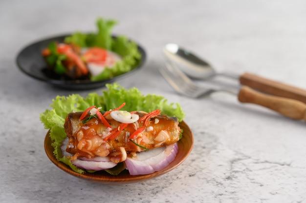 Salada de sardinha em conserva picante apetitosa com molho picante em uma tigela de madeira Foto gratuita