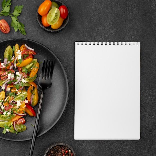 Salada de tomate com queijo feta, rúcula e caderno em branco Foto gratuita