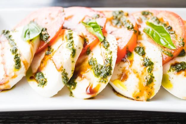 Salada de tomate e queijo mussarela em chapa branca Foto gratuita