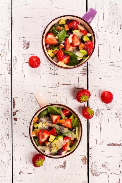 Salada de verão fresco com morango, abacate e espinafre no fundo de madeira rústico branco Foto Premium