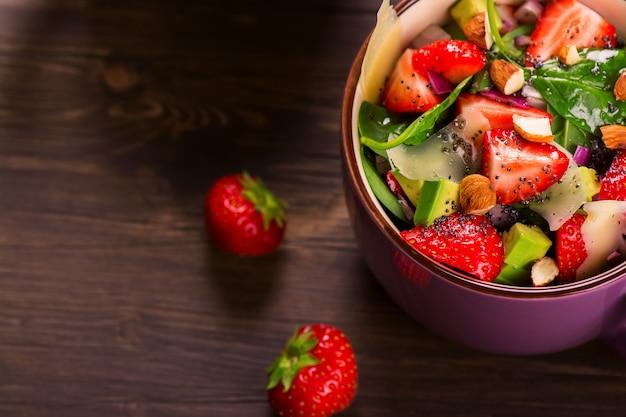 Salada de verão fresco com morango, abacate e espinafre no fundo de madeira rústico Foto Premium