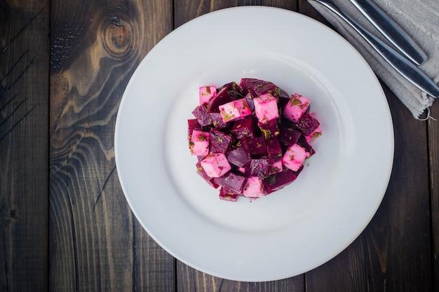 Salada de vista superior com beterraba e queijo feta no prato na mesa de madeira Foto Premium