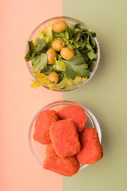 Salada de vista superior versus alimentos não saudáveis Foto gratuita