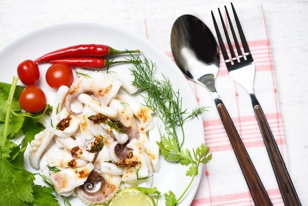 Salada do calamar com ervas e especiarias do limão na opinião superior de mesa de jantar. polvo cozido comida aperitivo quente e picante molho de pimenta. Foto Premium