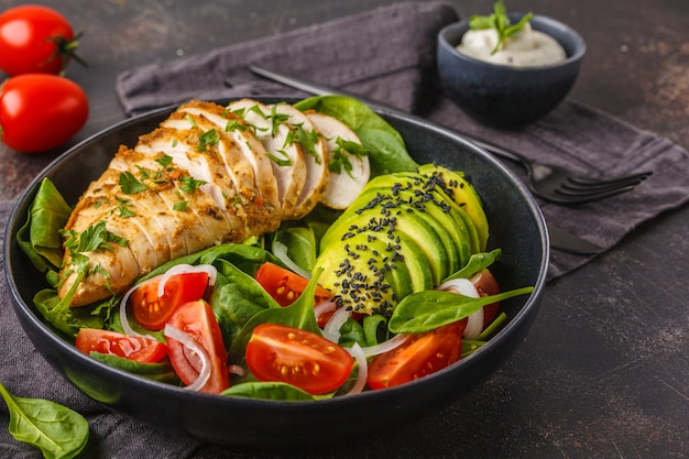 Salada do peito de frango e do abacate com espinafres, tomates e molho de caesar, fundo escuro. Foto Premium