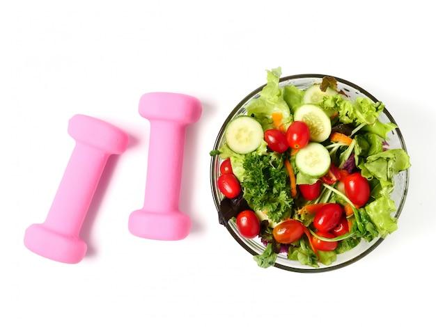 Salada dos legumes misturados e equipamento da aptidão no fundo branco. Foto Premium