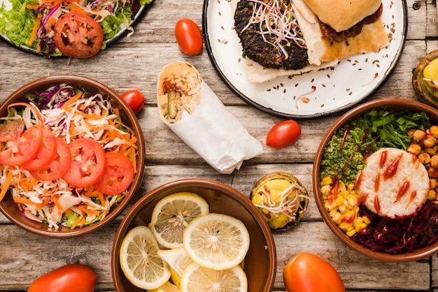 Salada; fatias de limão com hambúrguer; tigela de burrito e envoltório na mesa Foto gratuita