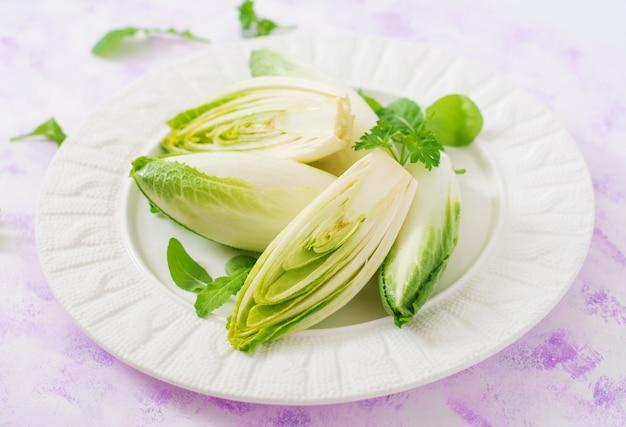 Salada fresca e saudável da chicória (witloof) em uma placa. menu dietético. comida saudável. Foto Premium