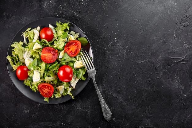 Salada fresca saborosa plana leigos na chapa preta com espaço de cópia Foto gratuita