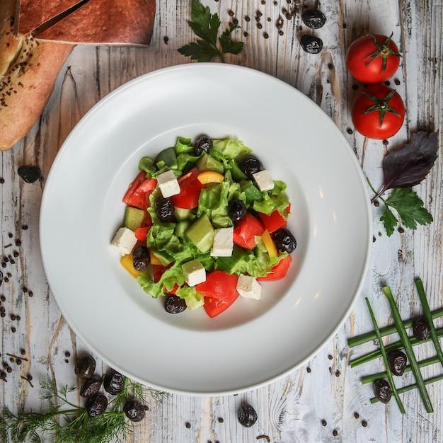 Salada grega em um prato com tomate, azeitonas, pão, ervas e especiarias Foto gratuita