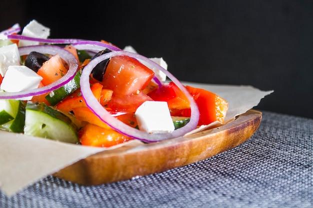 Salada grega em uma placa de madeira Foto Premium