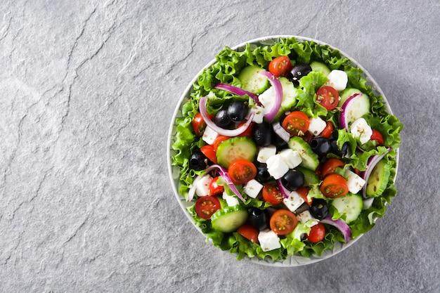 Salada grega fresca no prato com azeitona preta, tomate, queijo feta, pepino e cebola no espaço da cópia de vista superior de fundo cinza Foto Premium