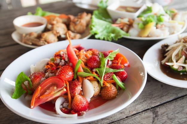 Salada picada de morango no prato branco, menu espacial na Tailândia Foto gratuita