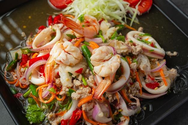 Salada picante de frutos do mar mistos com ingredientes de comida tailandesa. Foto gratuita