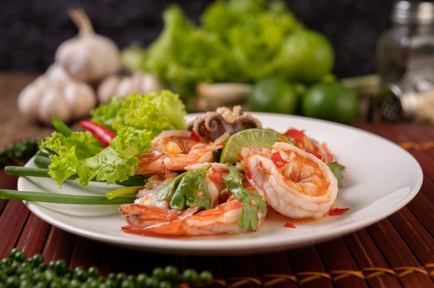 Salada picante de lula e camarão em prato branco com coentro de limão e alface Foto gratuita