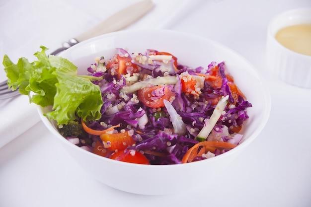 Salada primavera com repolho roxo, rabanetes, tomate, cebola na tigela branca Foto Premium