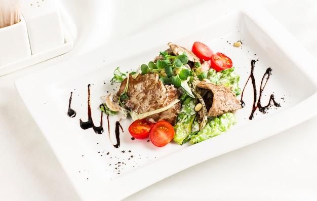 Salada quente com carne, cogumelos, tomates cereja, pinhões e ervas Foto Premium