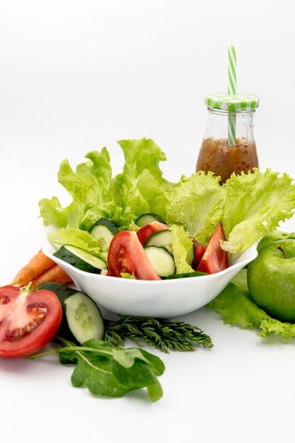 Salada saudável com suco contra o fundo branco Foto gratuita