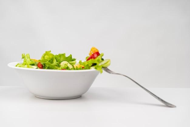 Salada saudável de vista frontal com garfo Foto gratuita