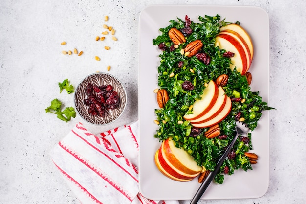 Salada saudável do vegetariano com maçã, arando, couve e noz-pecã em uma placa retangular, vista superior. Foto Premium
