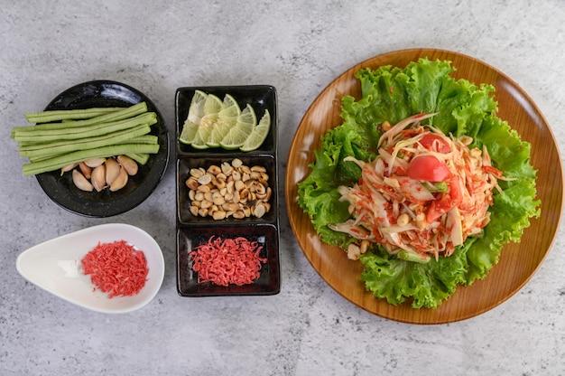 Salada tailandesa de papaia em um prato branco com feijão, alho e couve branca Foto gratuita