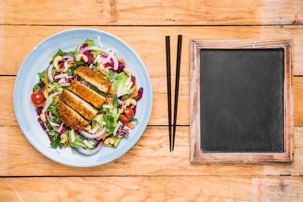 Salada thai chicken; pauzinho e ardósia em branco na mesa de madeira Foto gratuita