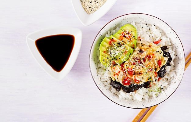 Salada vegana com arroz, repolho kimchi em conserva, abacate, nori e gergelim na tigela Foto Premium