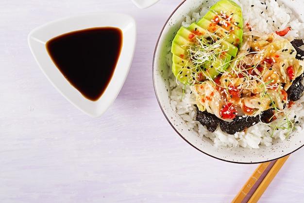 Salada vegana com arroz, repolho kimchi em conserva, abacate, nori e gergelim na tigela. Foto gratuita