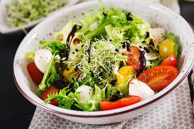 Salada vegetariana com tomate cereja, mussarela e alface. Foto gratuita