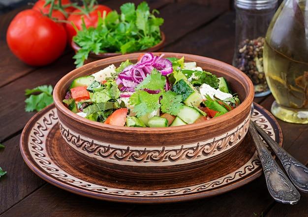Salada vegetariana com tomate cereja, queijo brie, pepino, coentro e cebola vermelha. cozinha americana. Foto gratuita