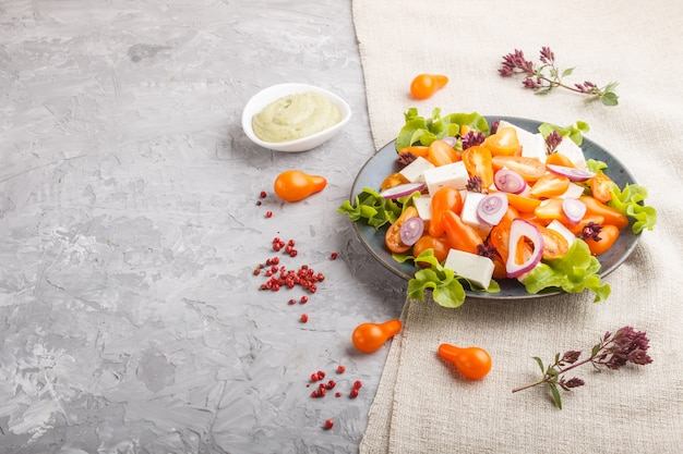 Salada vegetariana com tomates frescos de uva, queijo feta, alface e cebola, vista lateral. Foto Premium