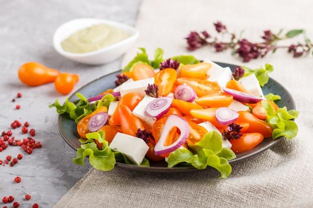 Salada vegetariana com tomates frescos de uva, queijo feta, alface e cebola, vista superior. Foto Premium