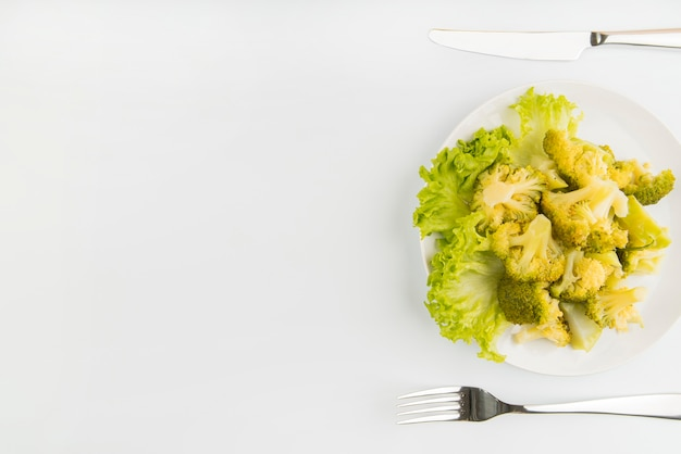 Salada verde de vista superior com talheres e cópia-espaço Foto gratuita