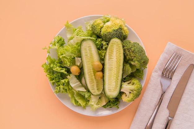 Salada verde de vista superior com talheres Foto gratuita