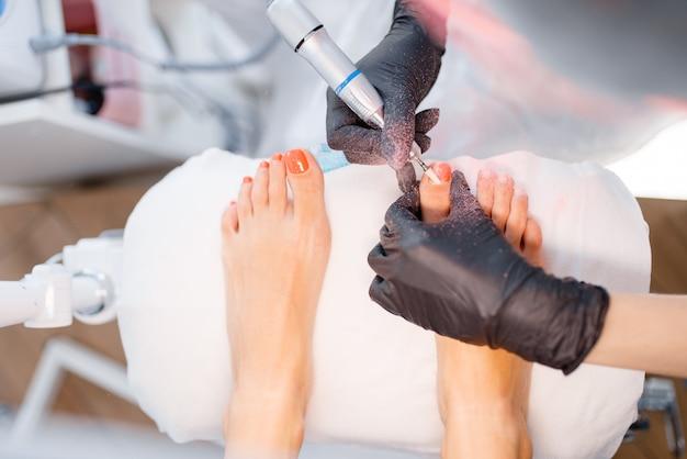 Salão de esteticista, pedicure, procedimento polonês. tratamento de unhas para cliente do sexo feminino em salão de beleza, médico em luvas trabalha com as unhas dos pés do cliente Foto Premium