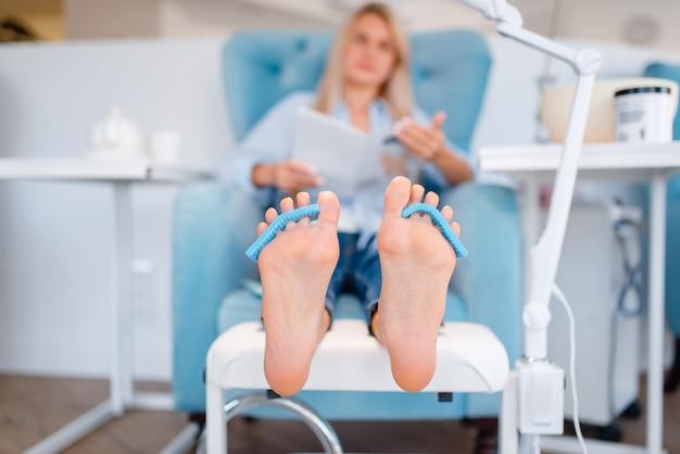 Salão de esteticista, procedimento de cuidados com os pés. tratamento de pernas para cliente em salão de beleza, cliente sentada na poltrona, relaxamento antes da pedicure Foto Premium
