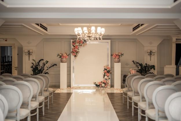 Salão do casamento. fileiras de cadeiras brancas festivas para os hóspedes. arco de casamento para a noiva e o noivo. Foto Premium