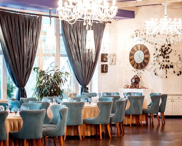 Salão do restaurante com cadeiras turquesas, paredes brancas, janelas francesas e cortinas Foto gratuita