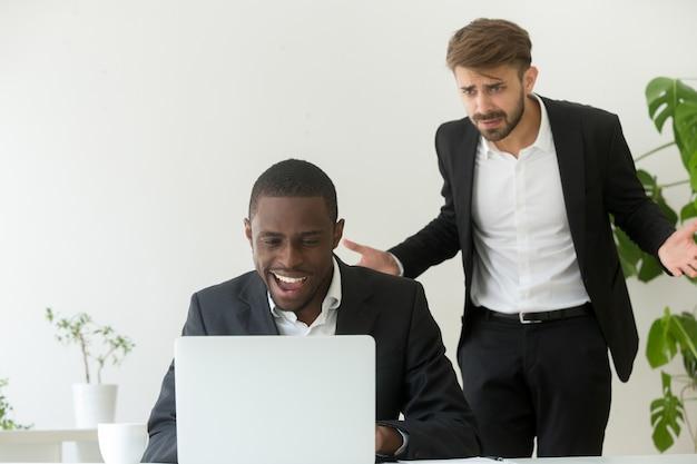 Saliência irritada que trava o empregado africano que entertaining em linha em vez do trabalho Foto gratuita