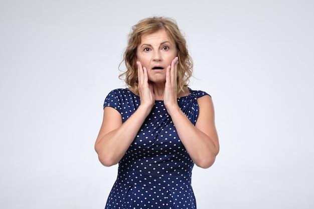 Salientou a mulher madura surpresa preocupada com rugas faciais Foto Premium