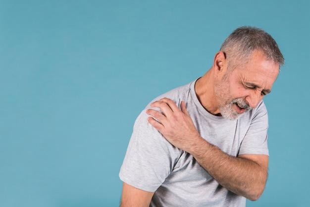 Salientou o homem sênior com dor no ombro em pano de fundo azul Foto gratuita