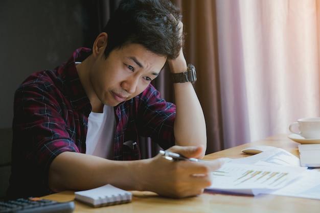 Salientou o homem. um jovem senta-se à sua mesa e mantém as mãos na cabeça por causa do estresse e relatório de resumo. Foto Premium