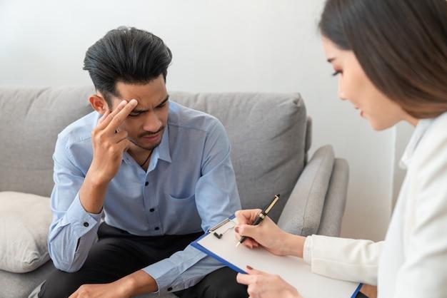 Salientou o paciente jovem asiático tem problema de vida sentado no sofá enquanto psiquiatra mulher escrevendo informações sobre sua doença Foto Premium
