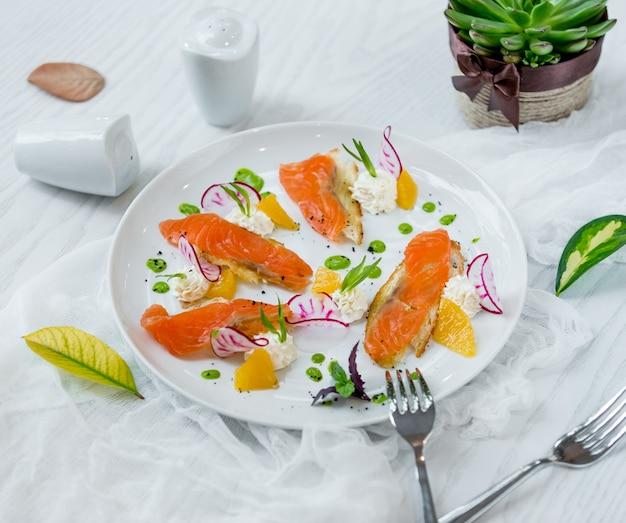 Salmão com fatias de laranja no prato Foto gratuita