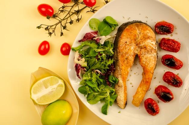 Salmão com tomate cereja assado e folhas de salada mista e metades de limão. comida mediterrânea. vista do topo Foto Premium