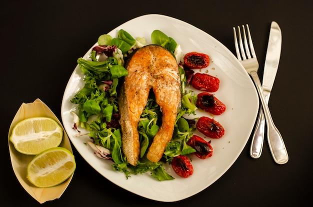 Salmão com tomate cereja assado e folhas de salada mista e metades de limão Foto Premium