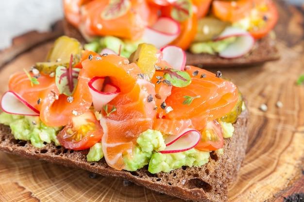 Salmão no pão de centeio com vegetais e ervas Foto Premium