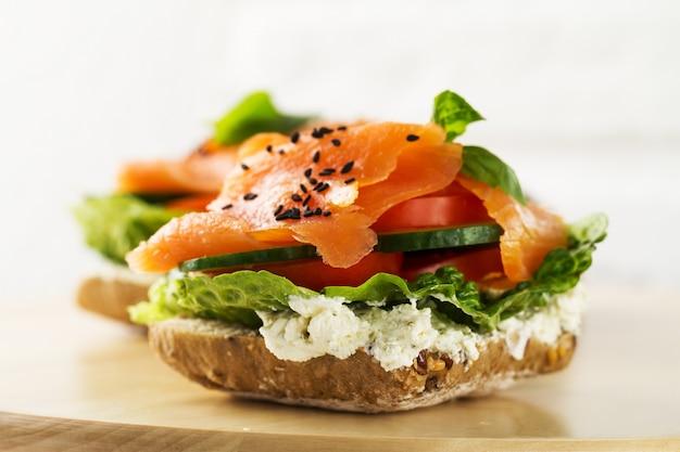 Salmão salgado saboroso colorido com vegetais no sanduíche. fundo brilhante. Foto gratuita