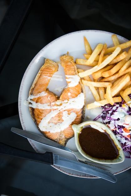 Salmões com colorido de receitas da salada na placa branca para o jantar - conceito saudável do alimento. Foto Premium