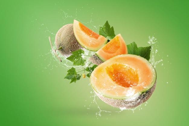 Salpicos de água em fatias de melões japoneses sobre fundo verde Foto Premium